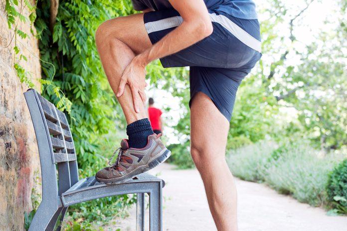 Runner holding lower leg
