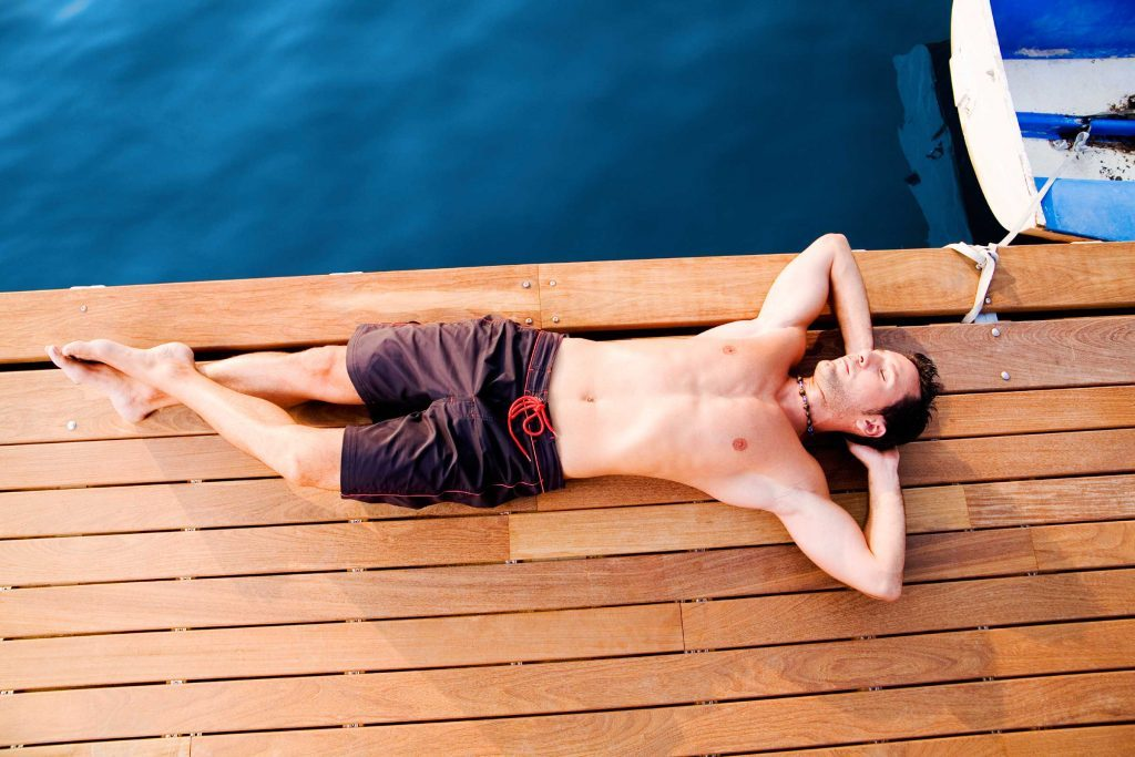 Man in swim trucks laying on the dock.
