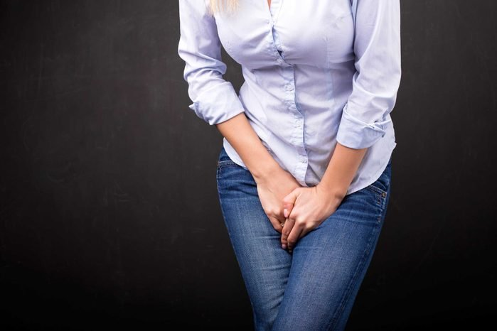 woman in jeans clutching her mid-section