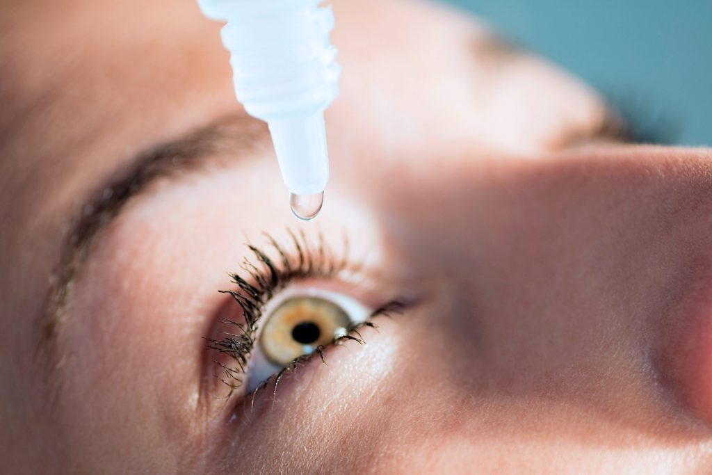 eye drop bottle with drop going into woman's eye
