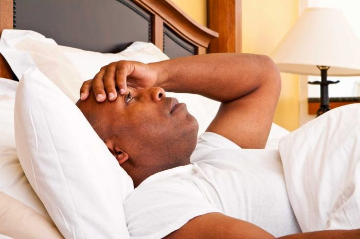 Man lying in bed resting on pillows holding his forehead with his left hand.