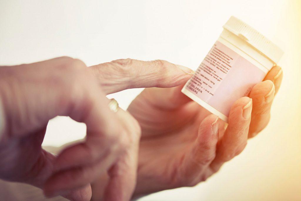 hands holding prescription pill bottle
