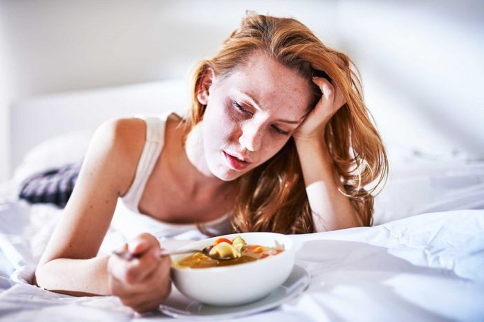 Woman lying on a bed eating a bowl of chicken soup and holding her forehead with her left hand.