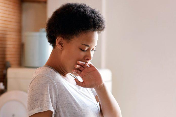 Woman stifling a yawn
