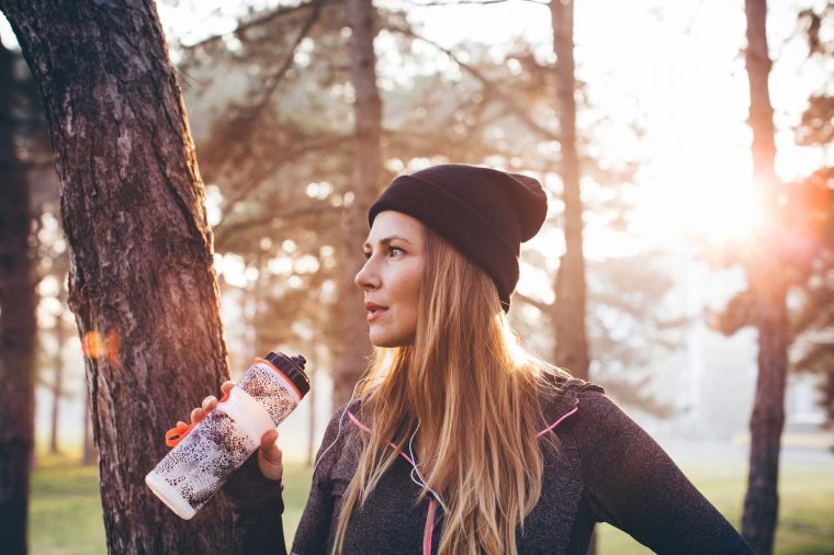 Woman runner wearing a beanie cap and drinking out of a water bottle while standing in a park.
