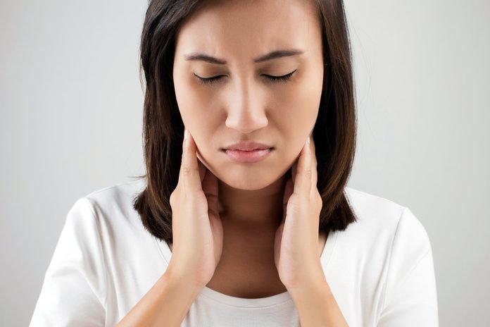 Woman in pain touching sides of her neck