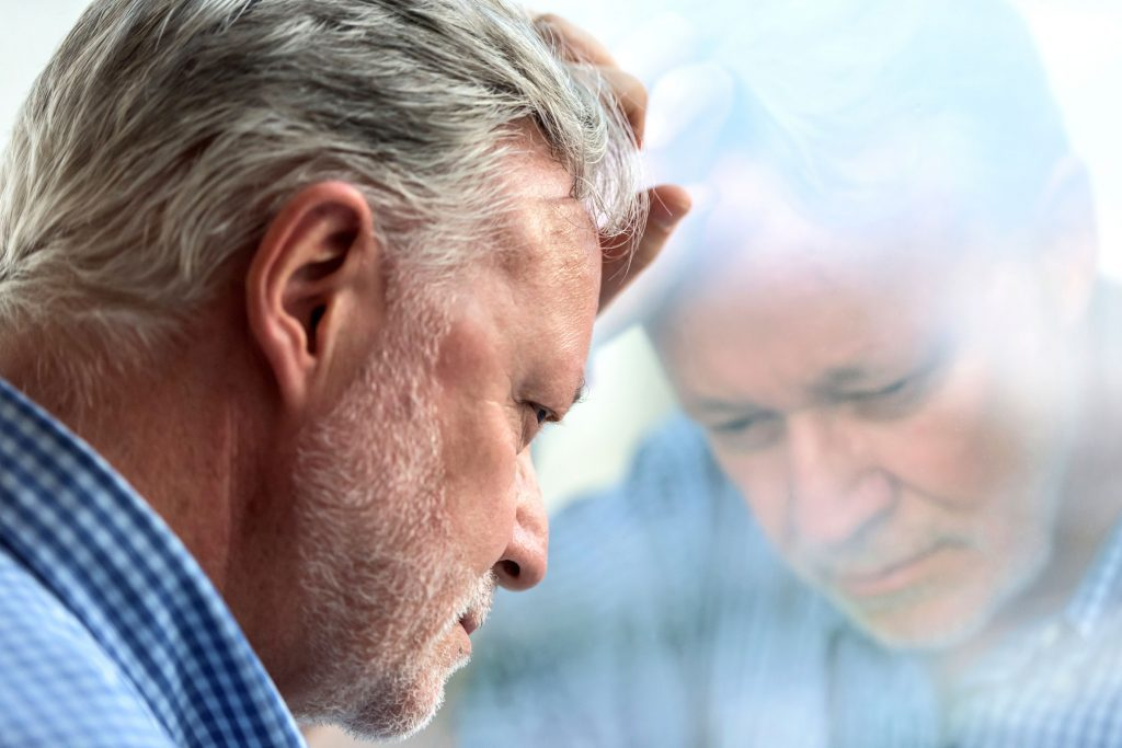 Older man contemplatively looking out a window
