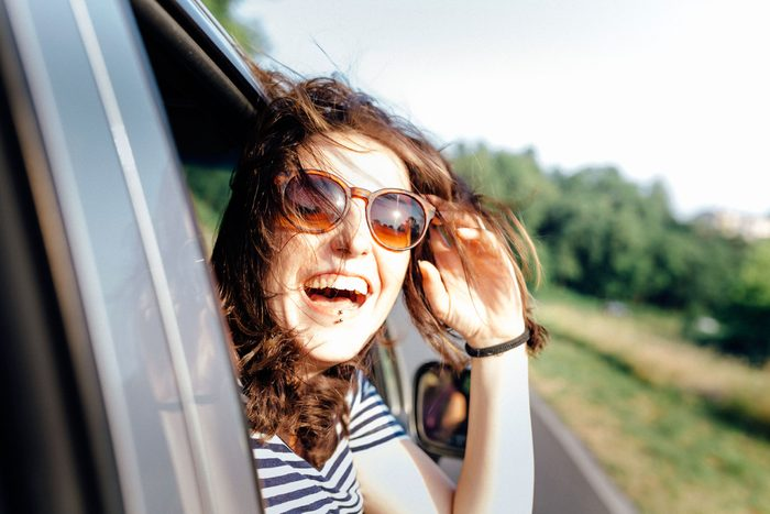 woman sticking head out car window