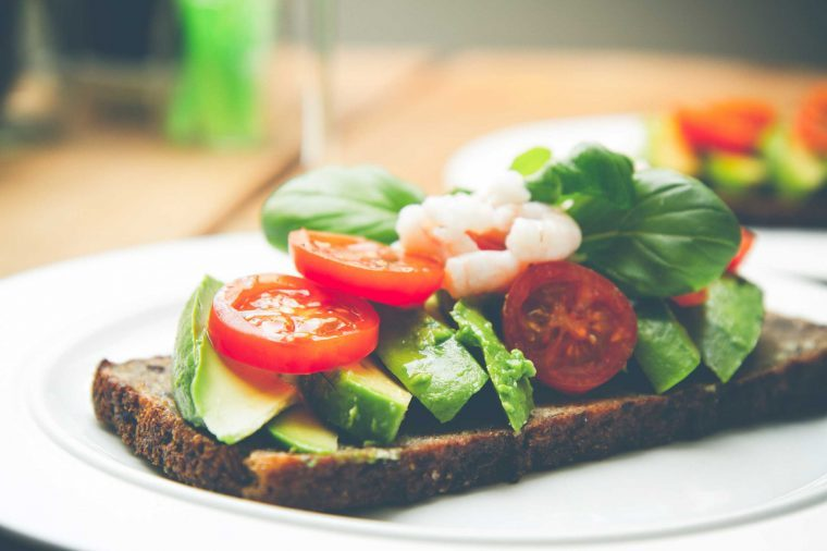 Vegetables like tomatoes and cucumbers piled on a piece of bread that's sitting on a plate.