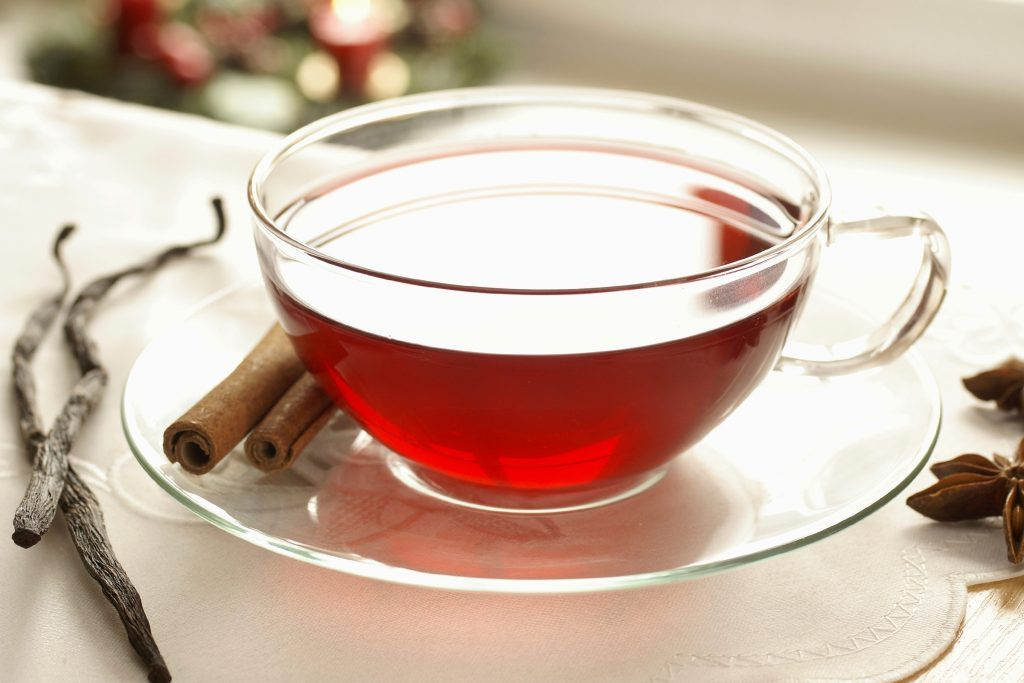 Red cup of tea with cloves and cinnamon.