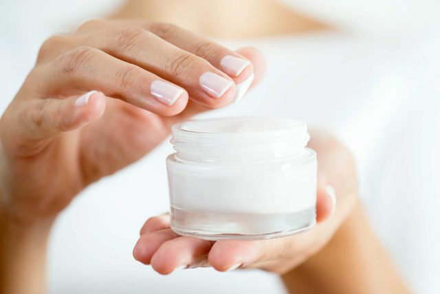 Woman dipping her fingertips into a jar of moisturizer.