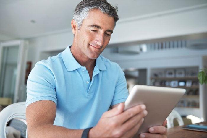 happy man looking at iPad