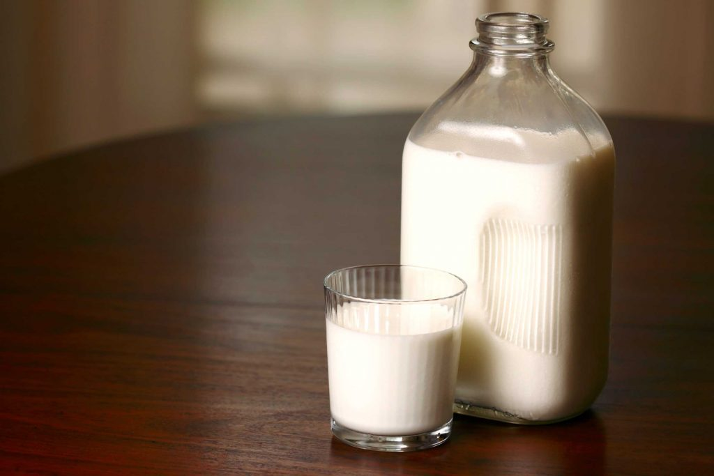 Glass of milk next to a glass bottle of milk.