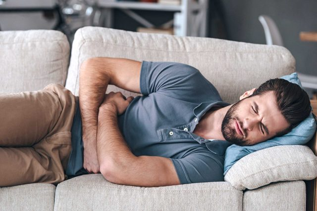 bearded man on his side on a couch, grimacing and holding his stomach