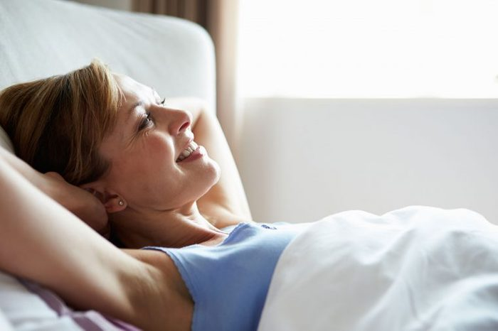 smiling woman with hands behind her head in bed