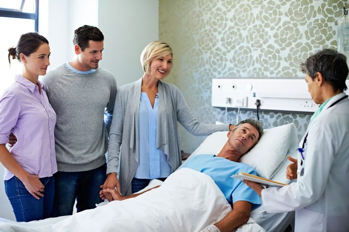 family and doctor at hospital patient's bedside