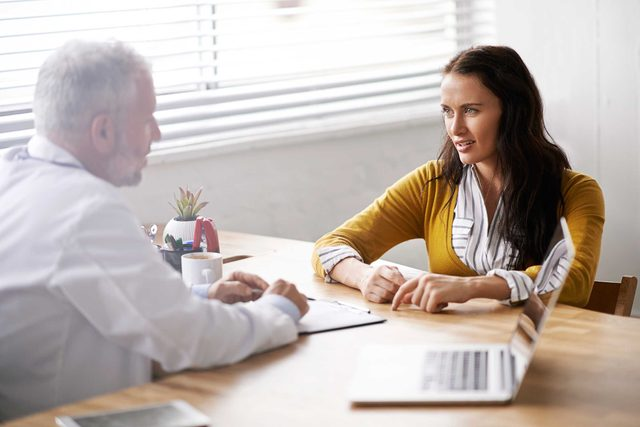 woman in conversation with an gray-haired doctor