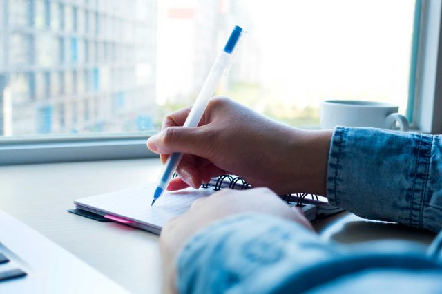 person writing on pad at desk
