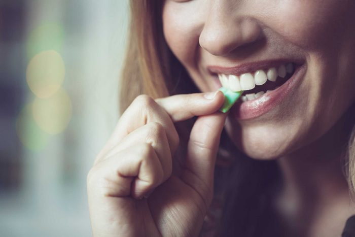 woman biting a piece of gum