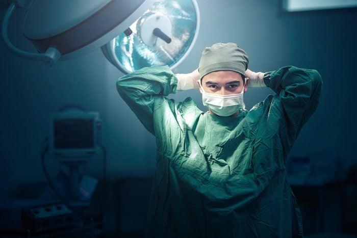 surgeon tying on face mask