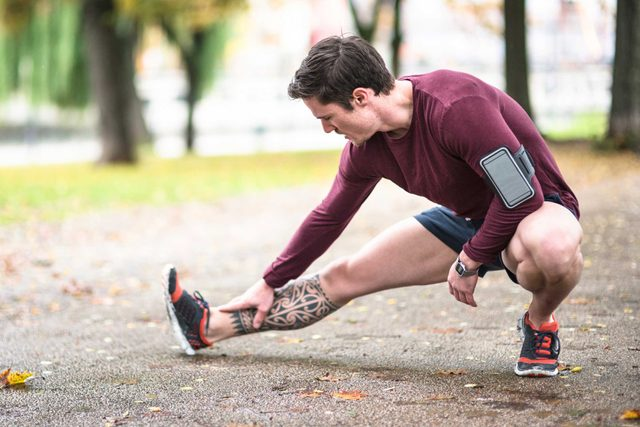 male runner stretching