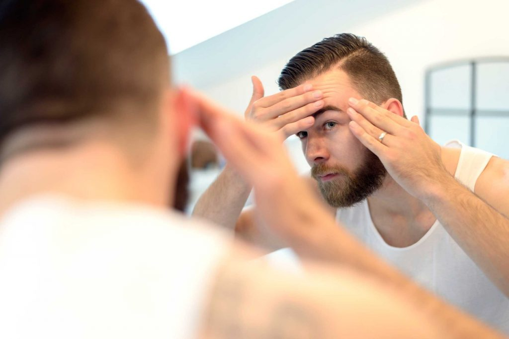 Man checking her forehead for acne in the mirror.