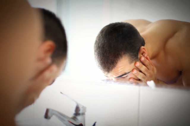 Man washing his face in the bathroom sink.