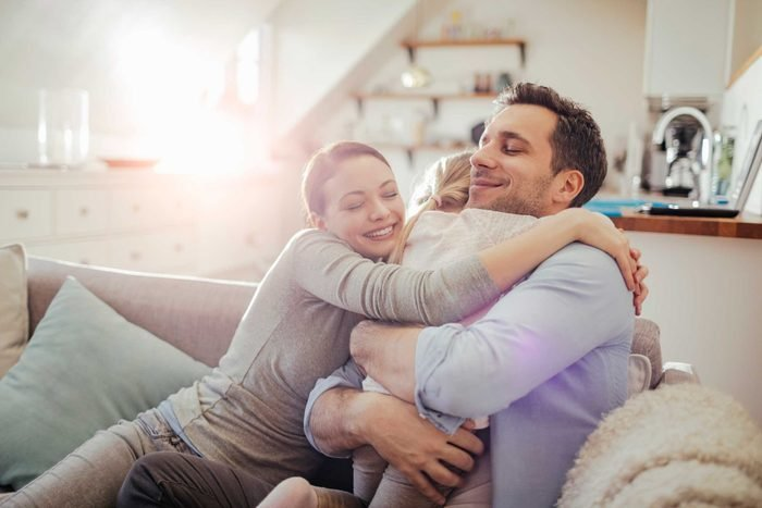 happy family, parents and child, hugging on couch