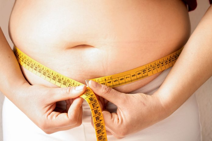 person measuring belly fat with tape measure