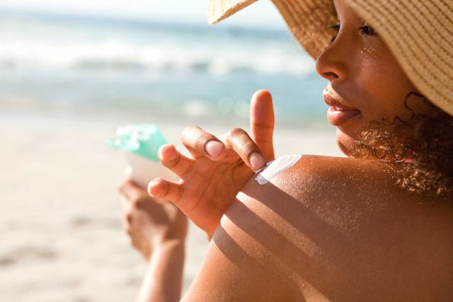 Dark-skinned woman applying sunscreen.
