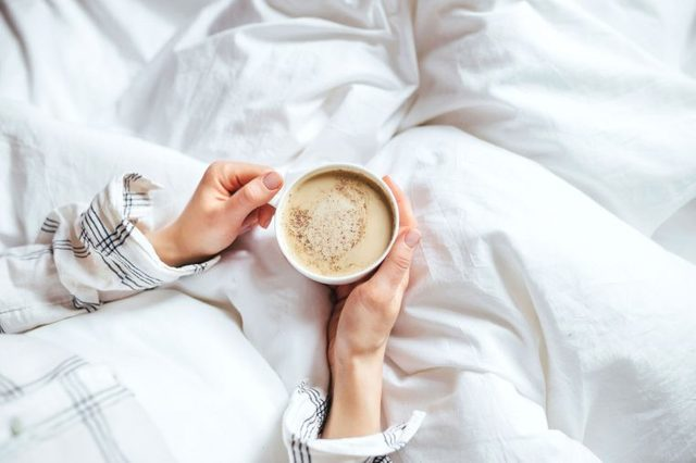 a person in bed holds warm drink