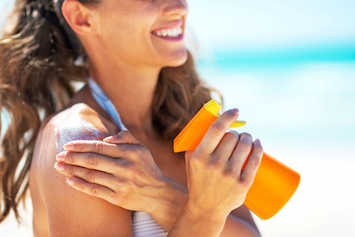 happy woman in swimsuit putting on sunscreen at beach