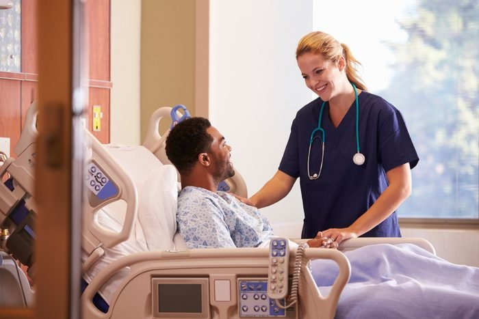 woman with stethoscope talking to patient in hospital bed