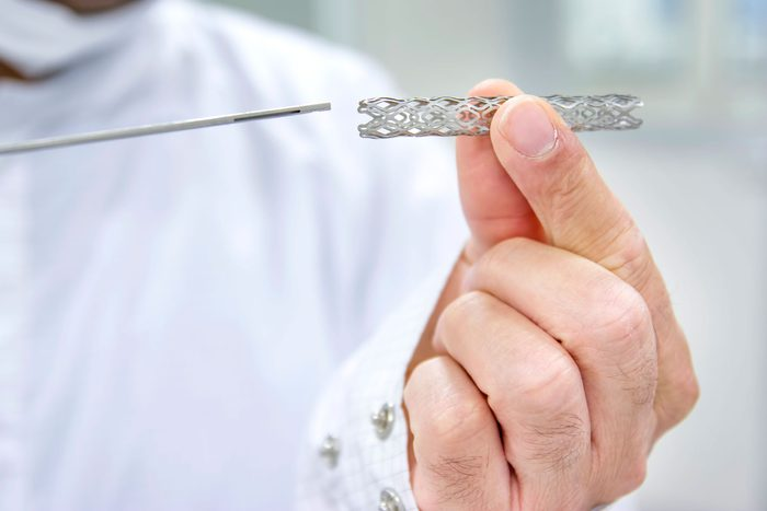 person holding metal stent