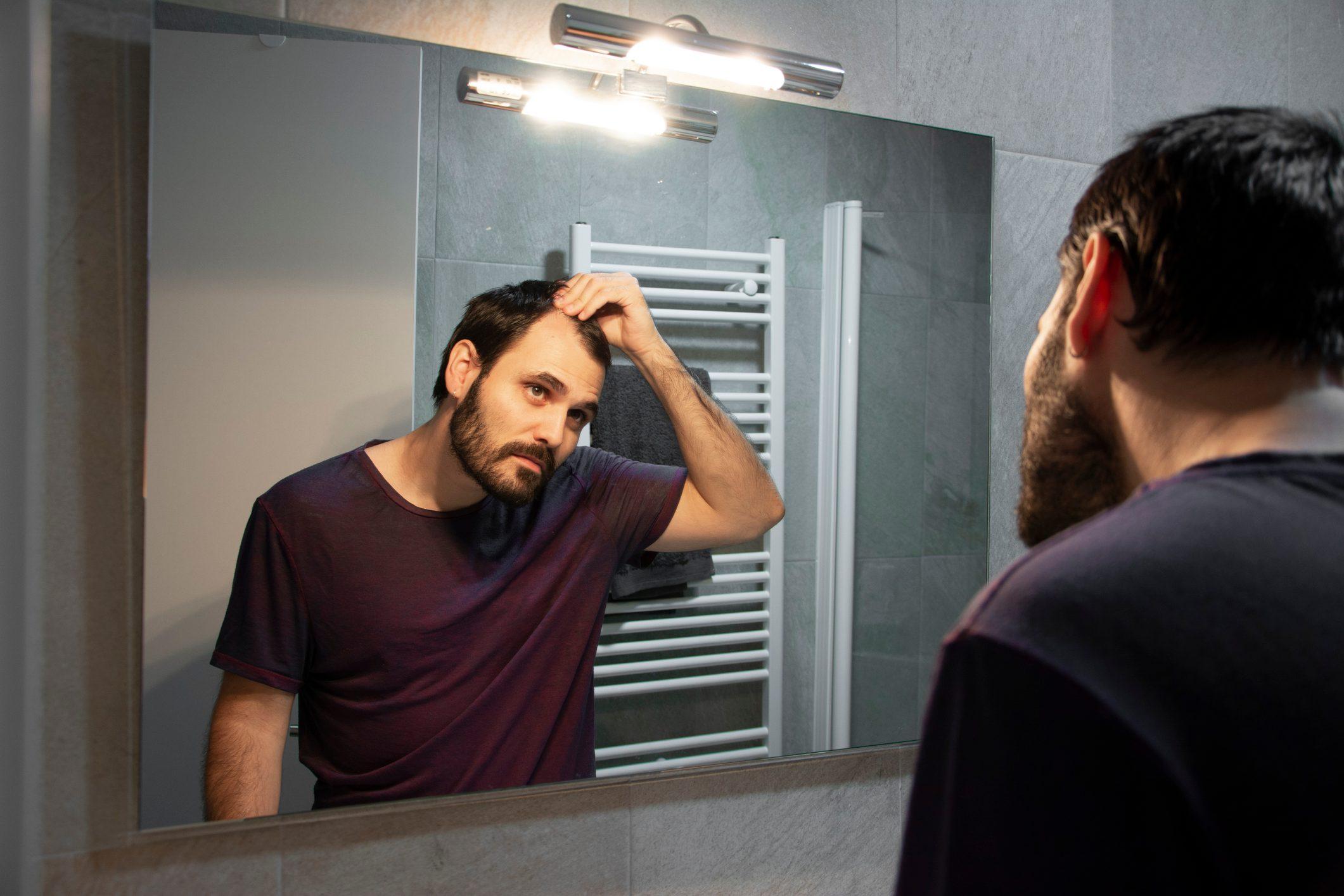 man looking at hair line in bathroom mirror