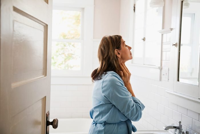 mature woman looking in the mirror in bathroom