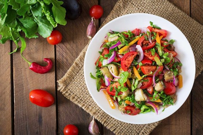 Plate of colorful veggies on a burlap placemat on a wooden table.