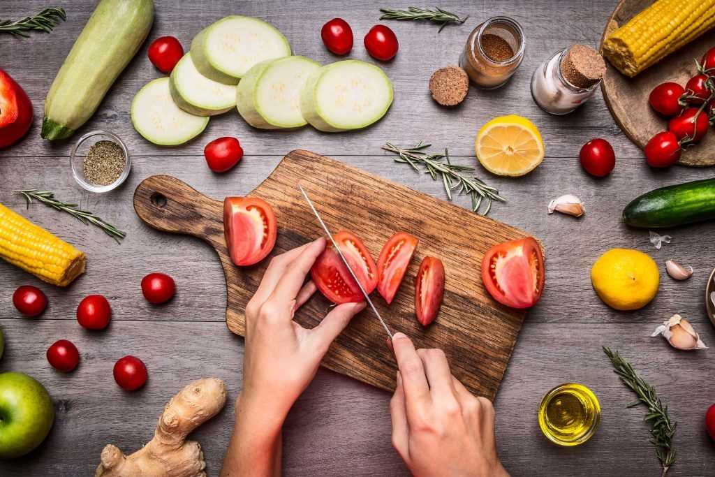 person cutting tomato on chopping board, surrounded by fresh vegetables