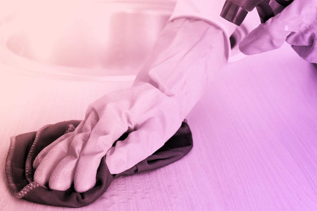 gloved hand cleaning surface