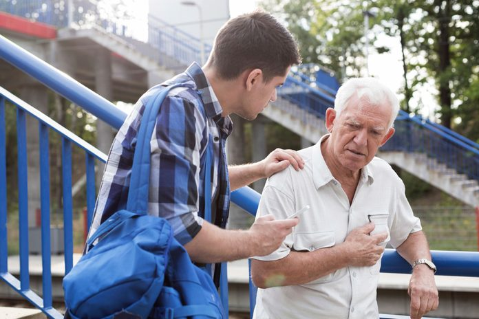 young man helping older man clutching chest