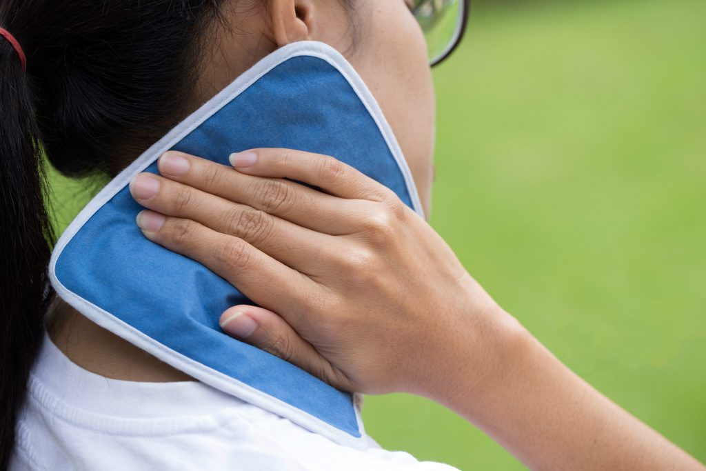 woman holding compress to her neck