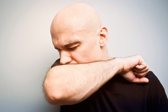 man with shaved head coughing into the crook of his arm
