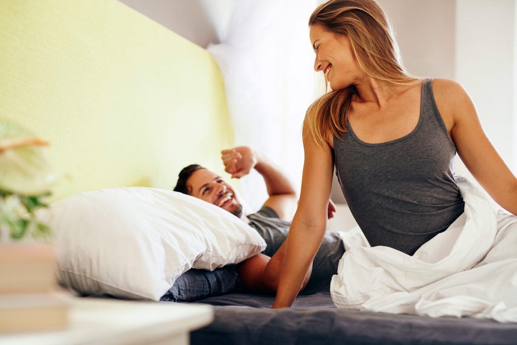 woman sitting up in bed looking at her partner