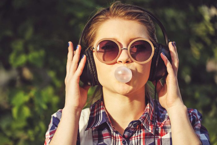 Young woman blowing a bubble with her chewing gum.