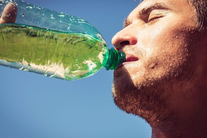 Man drinking a sports drink outdoors.
