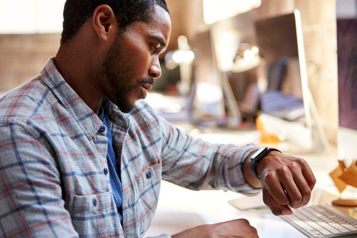 Black man checking his watch at his desk job