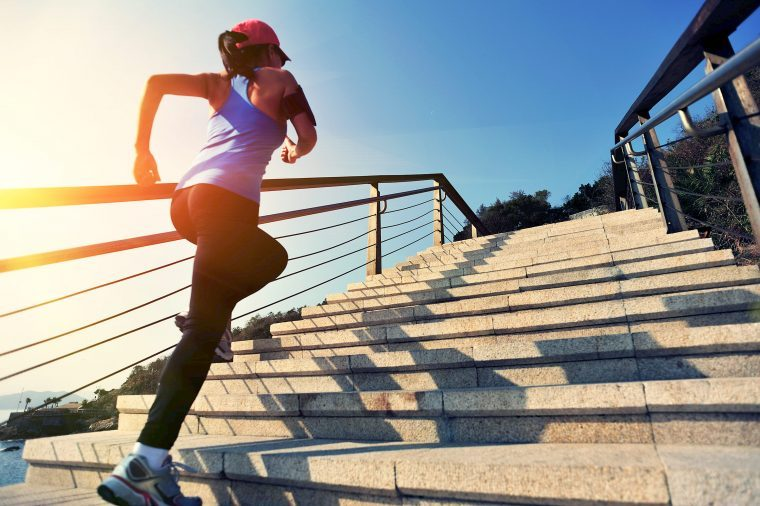 Woman in activewear jogging up a flight of outdoor stairs as the sun is rising.