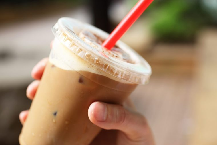 Person holding a plastic cup of iced coffee.
