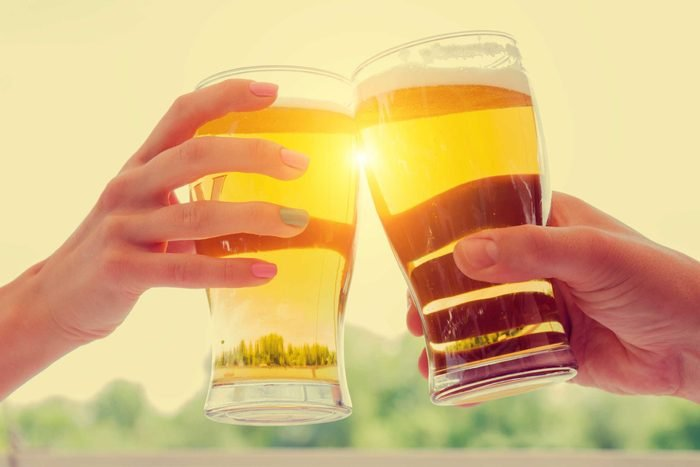 Two hands clinking beer glasses.