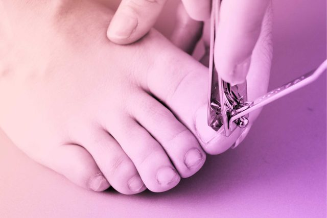 person using nail clippers on big toe